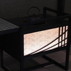 桜重ねの文様が浮き上がるLED内照式絹シェードの立礼棚